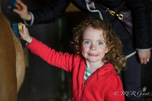 Image of girl grinning by horse