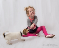 Girl and puppy playing with rope