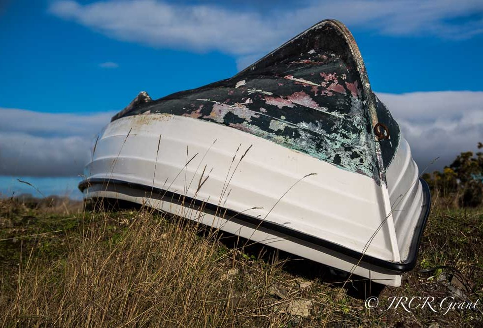 Upturned boat at the side of an estuary against a blue sky