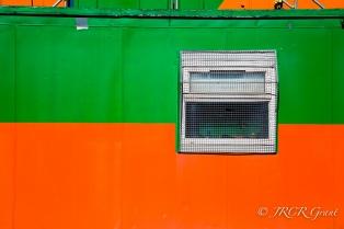 Window set into a bright portakabin of orange and green,