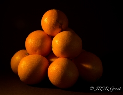 Oranges piled up with sun dancing on them