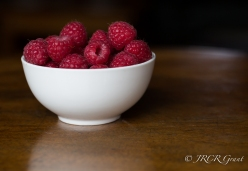 A bowl of raspberries atop a polished wooden table