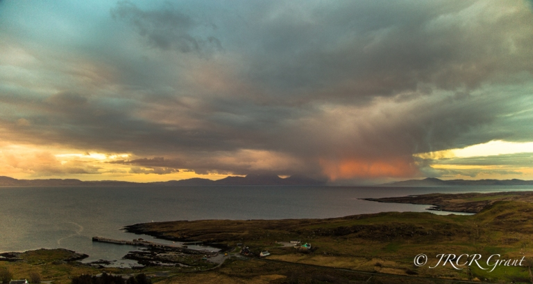 Jura and the Paps of Jura watch over a storm cloud lit pink by the early morning sun.