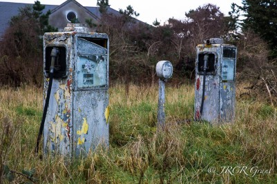 Two petrol pumps stand side by side, broken, peeling, but standing firm