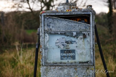 The old dials of a discintegrating petrol pump are stuck on gallons, shillings and pence