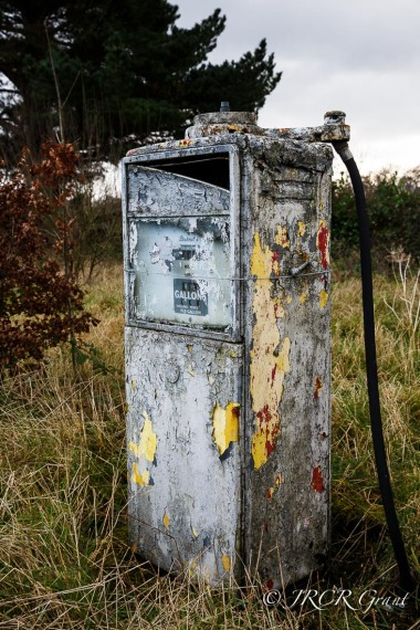 An old petrol pump stands negelcted, peeling in the shadow of a large tree and surrounded by untamed grass
