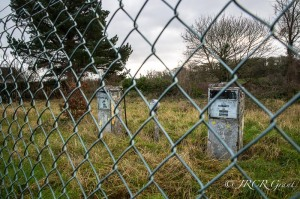 Old abandoned petrol pumps rise from the grass, imprisoned behind wire fencing.