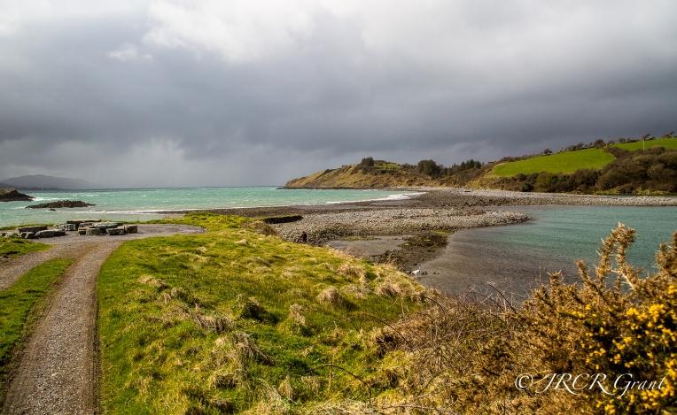 A storm approaches Whiddy Island, the sea turning aqua.