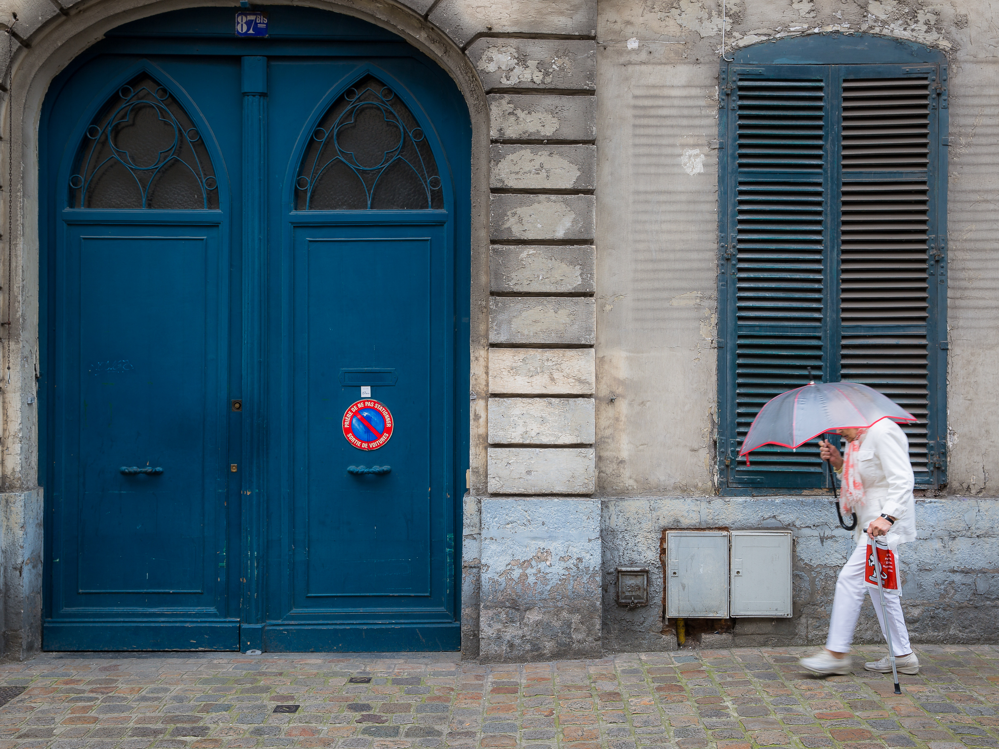 Lady walks across blue shutters and doors holding umbrella