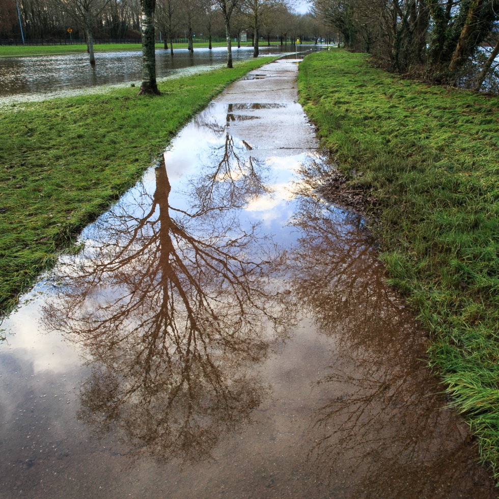 Reflections on the pathway by the River Lee, flooded with water
