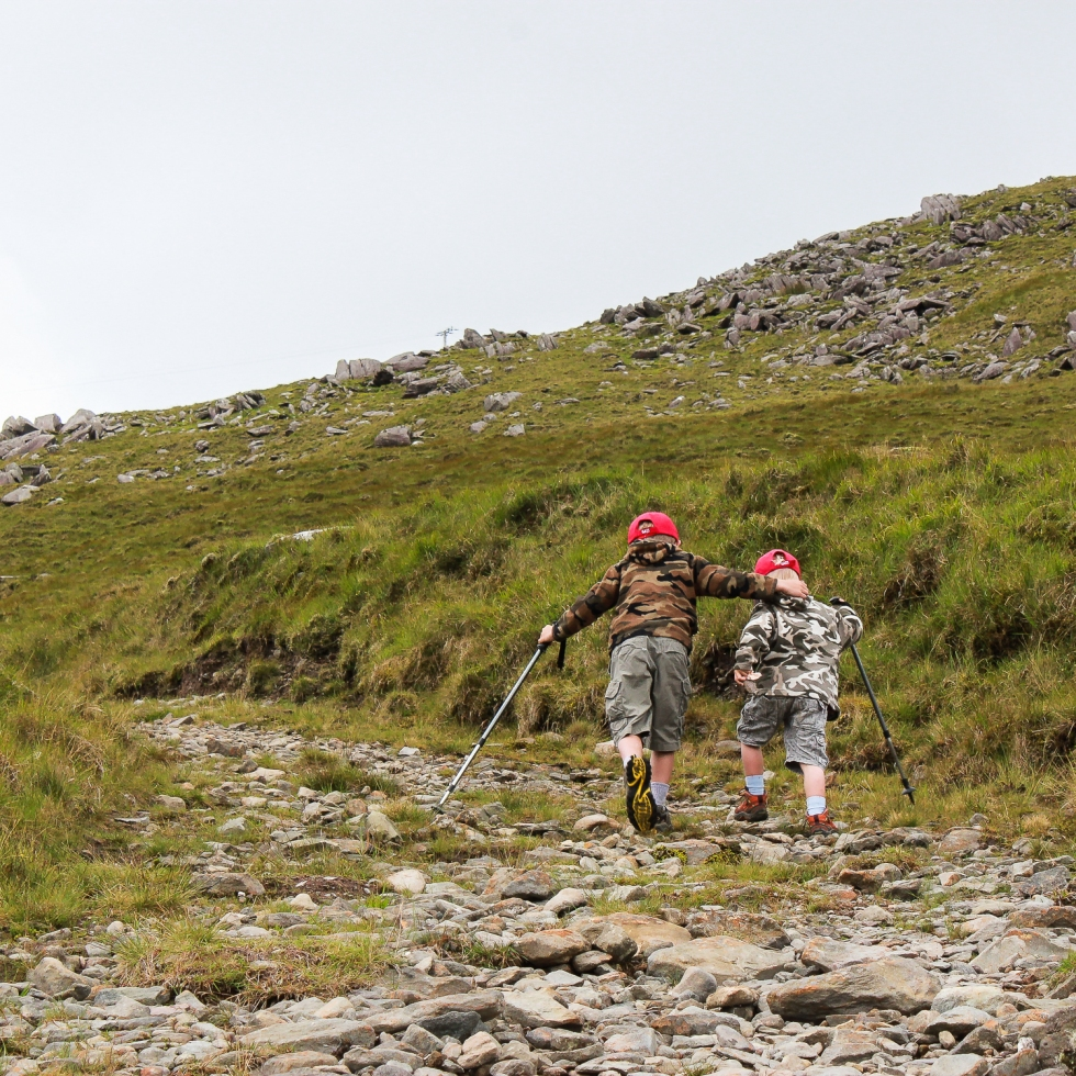 Older brother helps his sibling up the hill