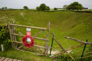 A wreath of poppies hangs on a wooden gate, beyond which lies the Lochnagar Crater