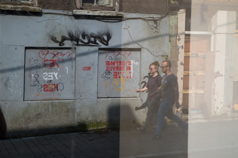 A man and a woman stride down Barrack Street, Cork City, caught in the reflection of an abandoned shop window