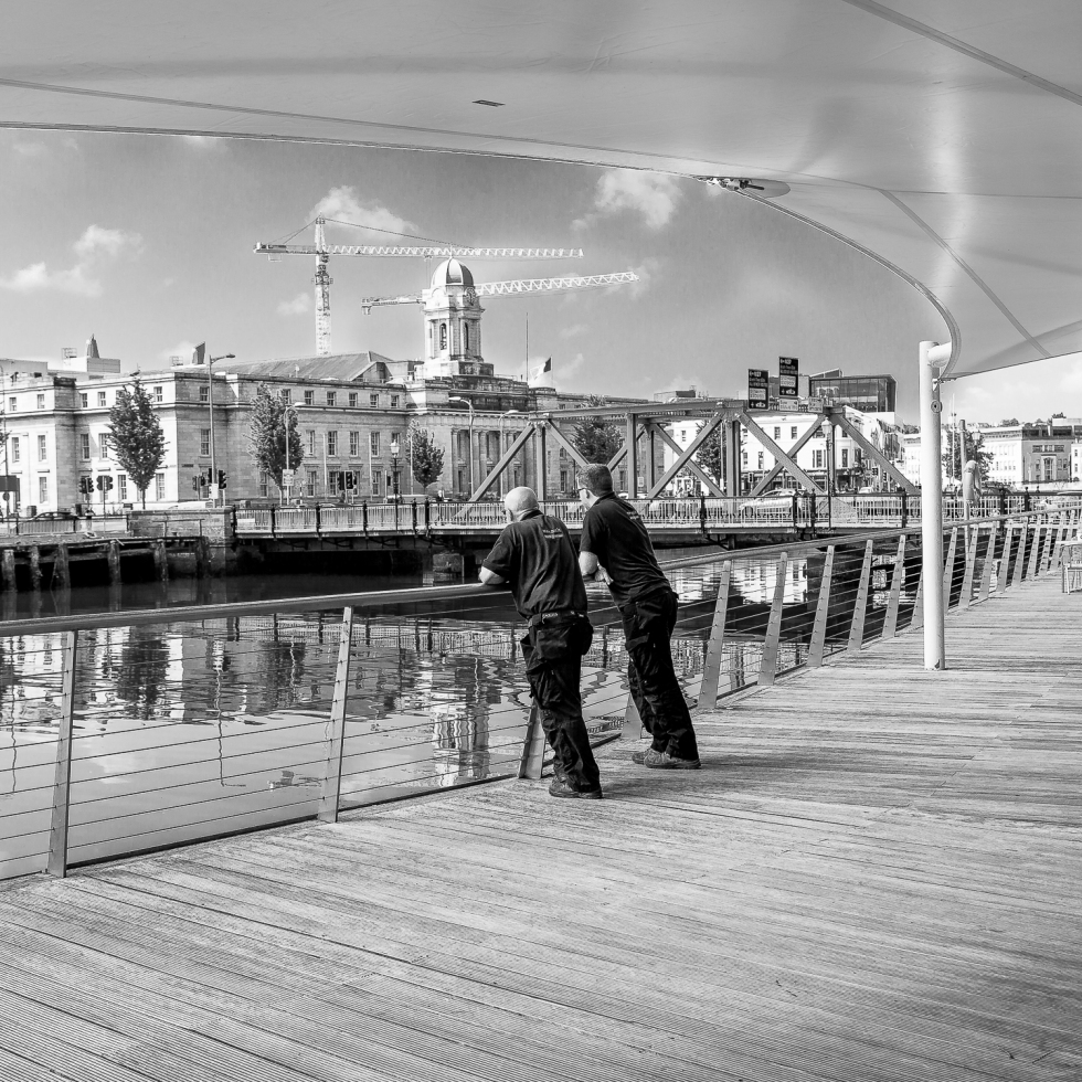 A suited man strolls along the boardwalk in Cork City while other workers take a break, leaning over the railing, cranes standing tall in the background.