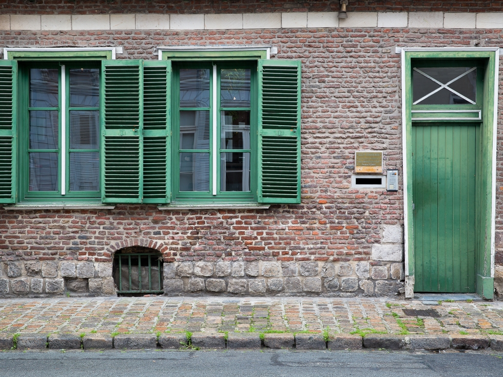 Green shutters and door on red brick in Lille, France