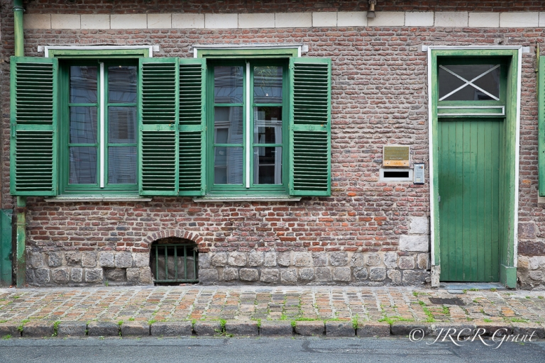 Green shutters and door adorn a red brick house in the old quarter of Lille, France