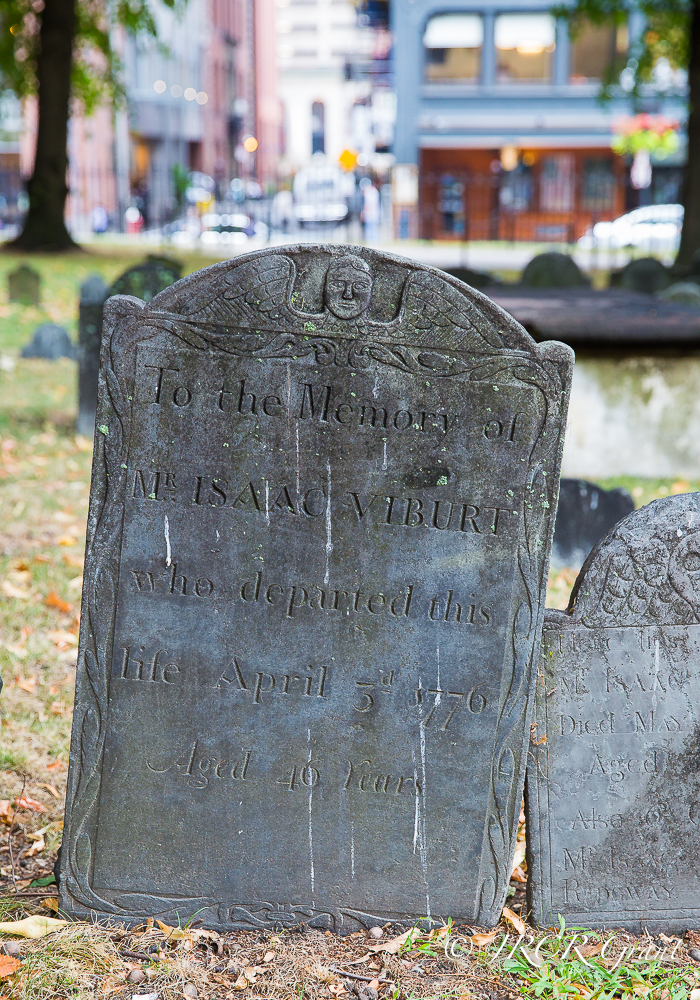 An old gravestone stands solid in the Granary burial ground as the City of Boston rushes by