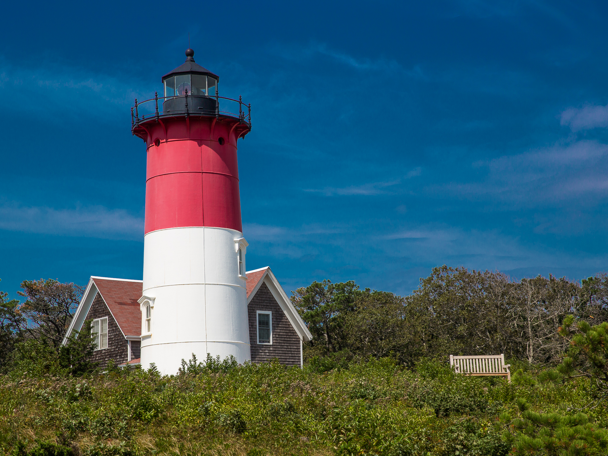 Nauset Lighthouse stands against a solid blue sky