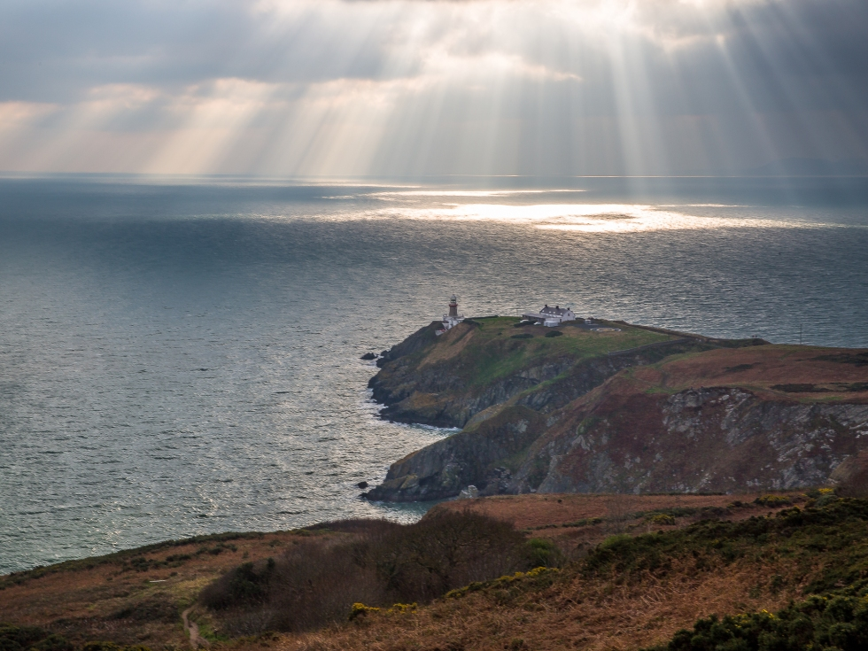 Howth Head Lighthouse with rays of sunshine dappling the sea