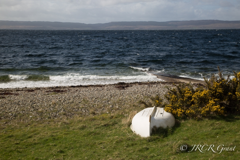 upturned dinghy on shore at Catacol, Isle of Arran, Scotland