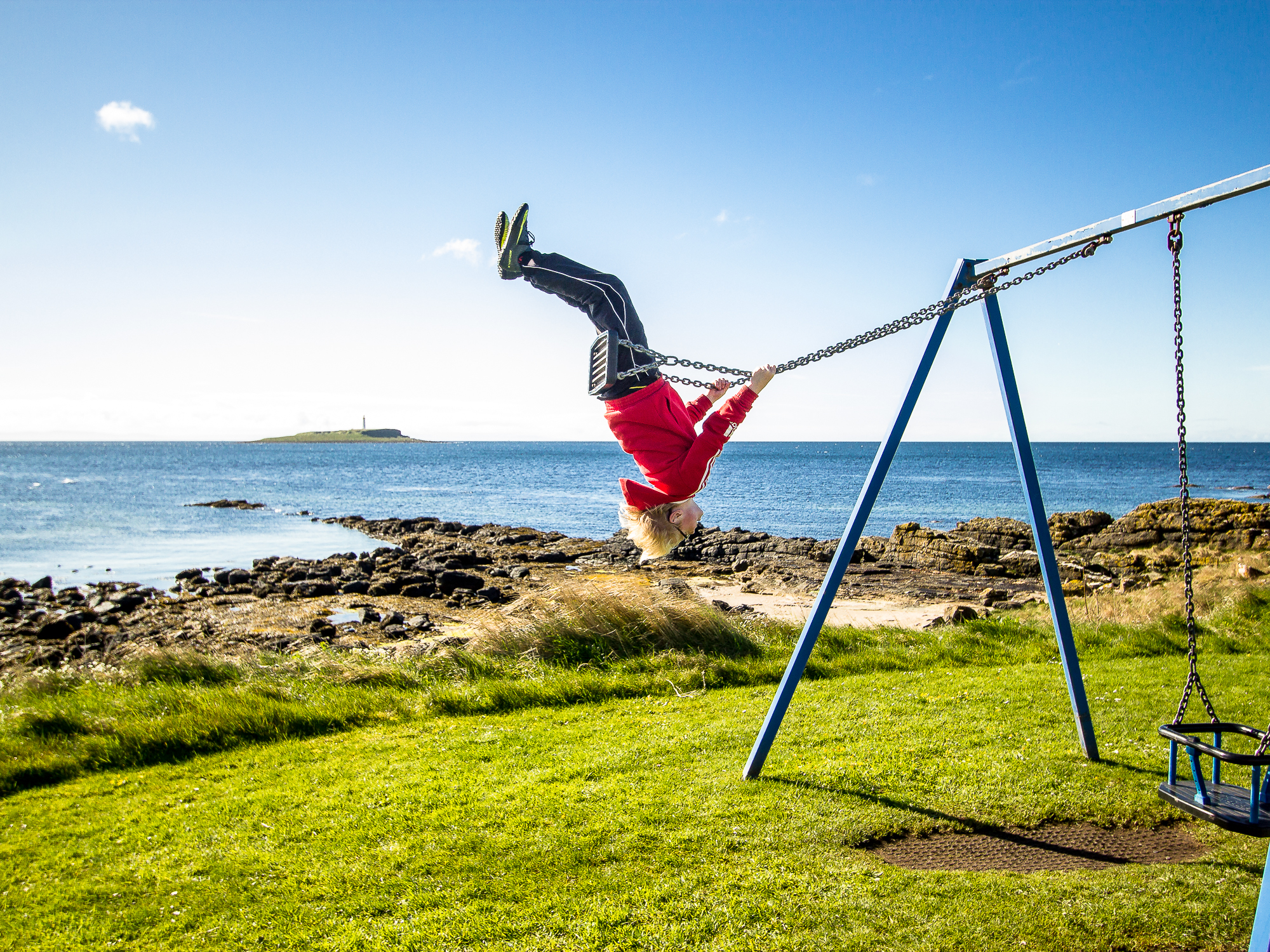 A young man flies high on a swing on the island of Arran
