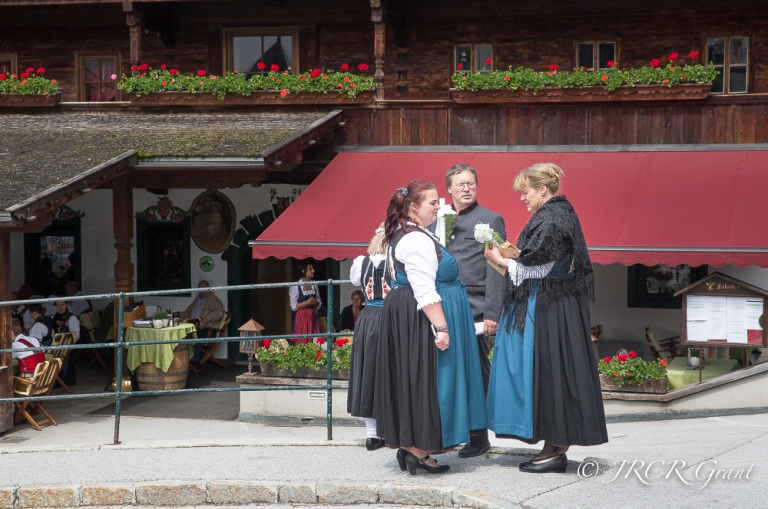 Men and woman in traditional dress in front of an Inn