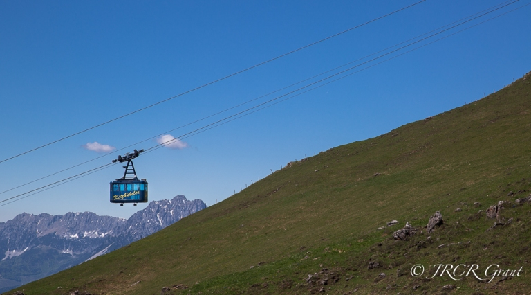 A cable car carries hikers to the top of the mountain