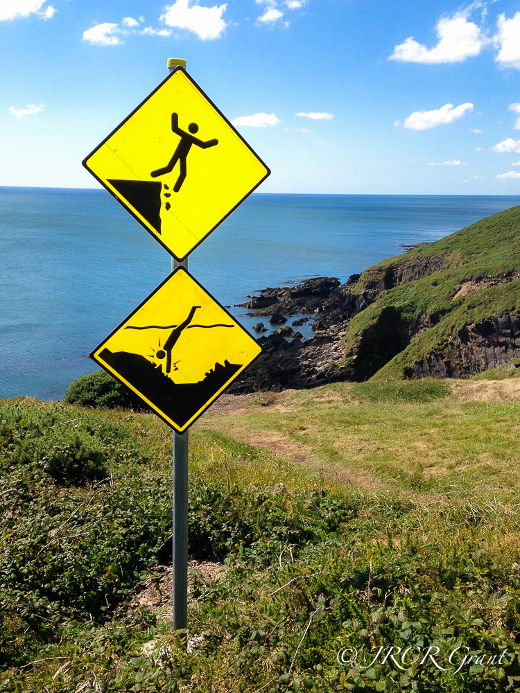 signs at Ballycotton warn of the danger of the cliffs and cliff diving