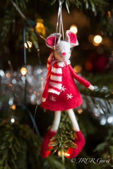 A dressed mouse hangs from a Christmas tree