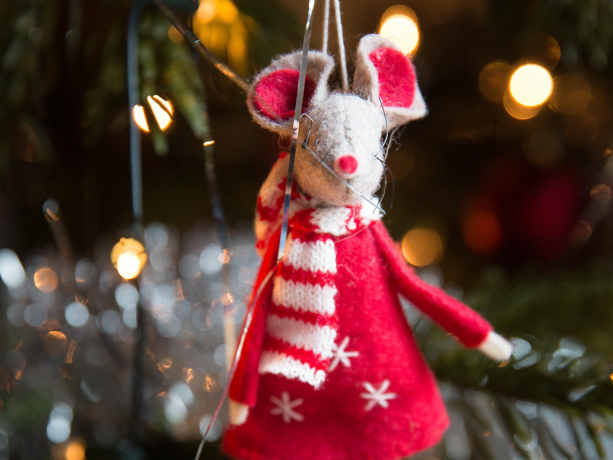 A knitted mouse ornament on a Christmas tree