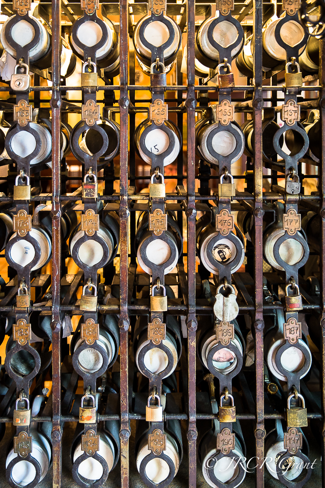 The steins of regulars are stored in racks in a Munich beer hall, each stein being guarded by a padlocked cage
