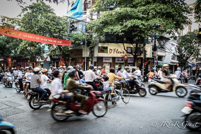 A cyclist walks her bicycle through a stream of mopeds in Hanoi, Vietnam