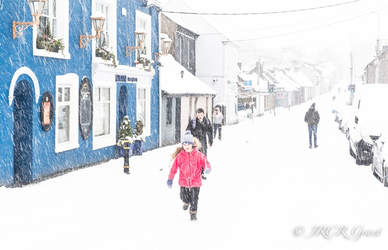 A girl skips in the snow in Ballintemple, Cork City, Ireland