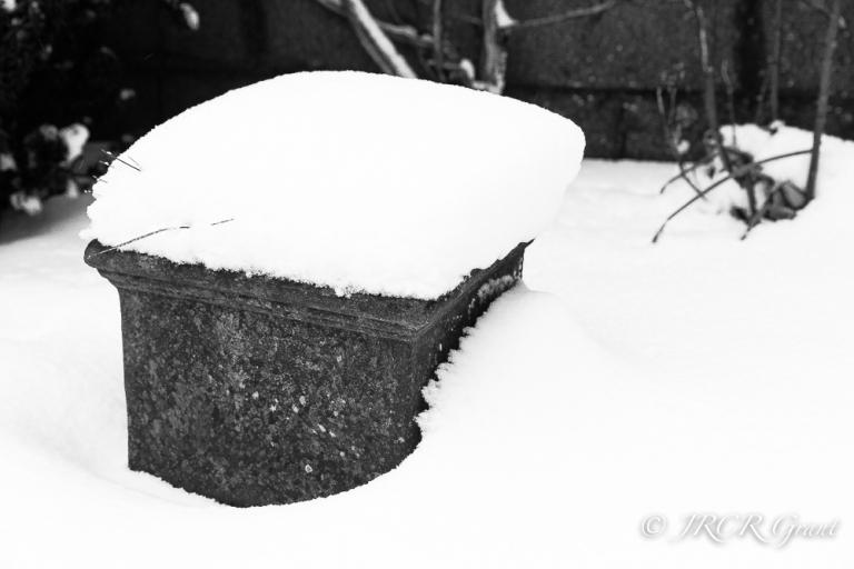 Snow wraps itself around a garden plant pot