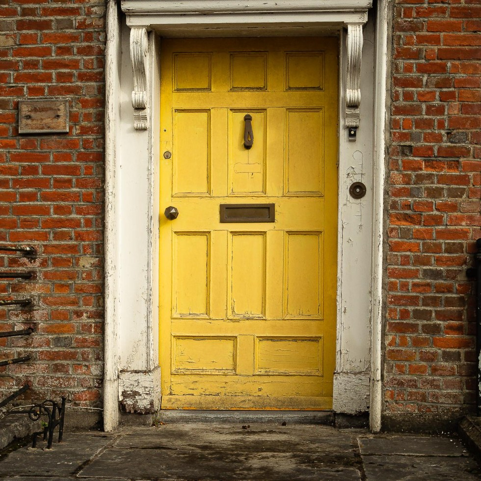 A faded yellow georgian door in Fermoy County Cork