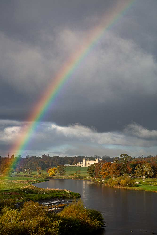 A rainbow adds brightness to a scene of the River Tweed and Floors Castle in the background