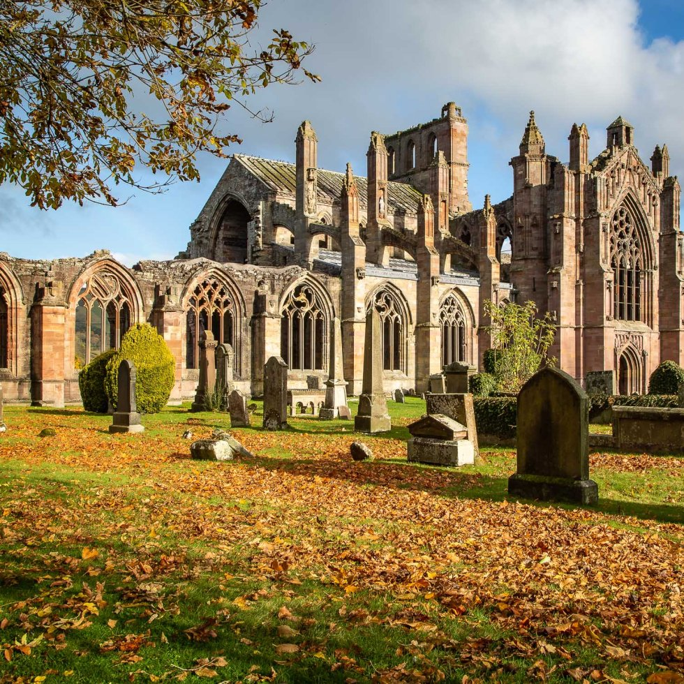 copper leaves litter the floor as Melrose Abbey stands proudly in the background.
