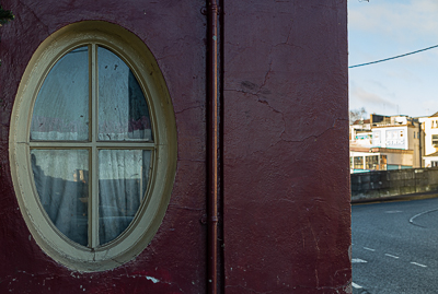 The dull oval window of an old bar besides the River Lee on George's Quay, Cork City