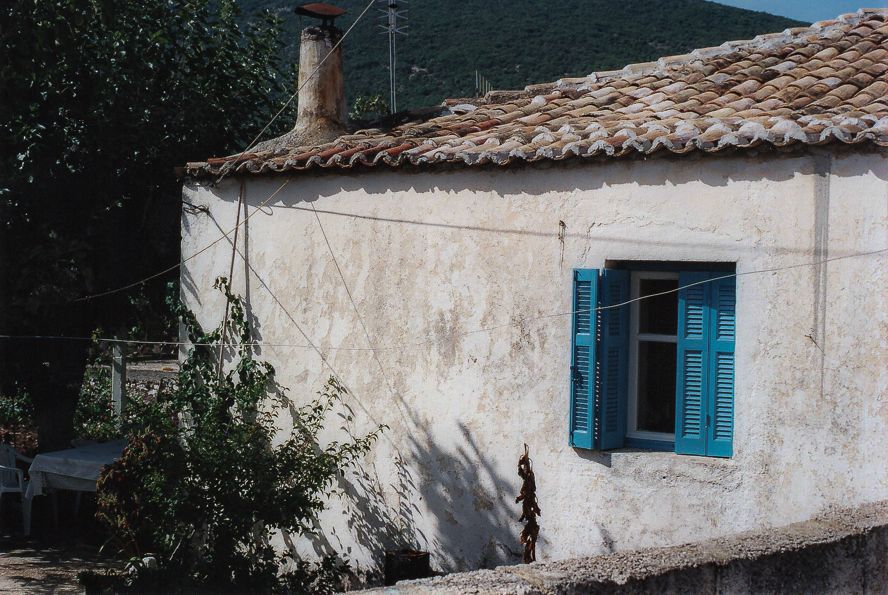 A white-washed cottage with blue shutters on the Island of Nidri
