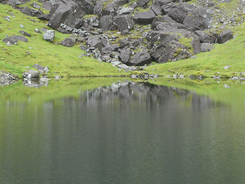 The bright green and rock greys are reflected in the rippled surface of Lough Cummeenoughter, Carrauntoohil