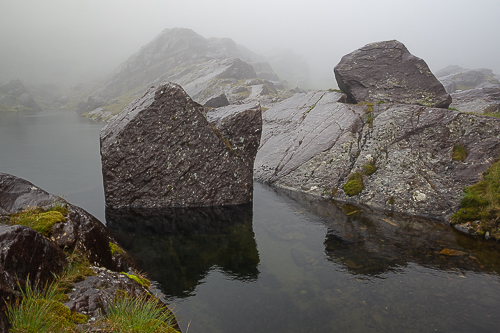 A boulder sits in the middle of a small lake, cast in mist