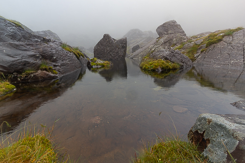A large boulder sits in the middle of a mist shrouded corrie lough