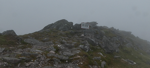 A warning sign near the summit tells hikers not to step further due to the sheer cliffs