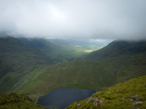 A cloud curtain hangs over the McGillycuddy Reeks obscuring the view of the Bridia Valley with Lough Curraghmore in the foreground.